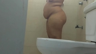 Young girl with big posterior bathing, cleansing her posterior and rubbing her wet vagina